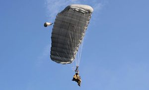 Airborne Systems Intruder RA-1 Army Ram Air Parachute system for military special forces and beginner jumpers. Carries 450 lbs. Max deployment altitude 25,000 ft. Canopy and blue sky.