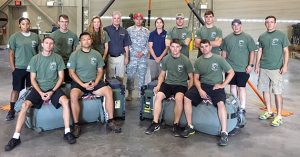 Airborne Systems - Military Parachute Training. Troop and cargo parachute certification for army riggers & jumpers. Instruction for oxygen and JPADS systems. 11 students 3 faculty in two rows, front row seated. 11 men, 3 women.