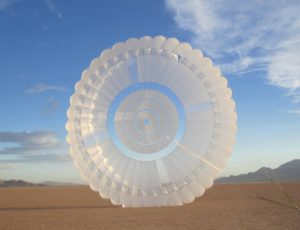 Airborne Systems top of parachute viewed touching ground in desert, blue sky. Military & space textile manufacturing & design. Army & space parachute canopies, aerial delivery (GPADS / JPADS). Aircraft & spacecraft deceleration systems.