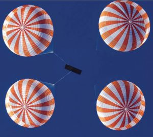 Airborne Systems space parachute & inflatable systems. Military-grade deceleration, airbag landing, aerospace recovery, personnel & cargo delivery parachute systems. Entry, Descent & Landing System (EDLS) development for space and high altitude applications. Recovery system for the Discoverer XIII reentry capsule. Three red and white striped canopies from below with blue sky.
