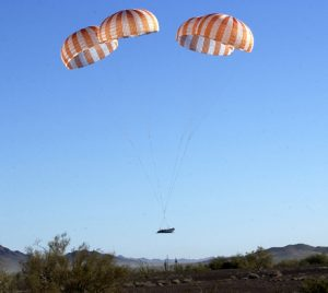 Airborne Systems Space Textile Manufacturing & Military Parachutes. Inflatable parachute systems for spacecraft. Custom design and development of military-grade Entry, Descent & Landing Systems (EDLS) for commercial spacecraft. Red and white striped canopies with cargo landing.