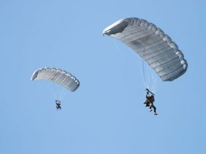 Airborne Systems - Intruder RA-1 Army Ram Air Parachute system for military special forces and beginner jumpers. Carries 450 lbs. Max deployment altitude 25,000 ft. 2 jumpers open canopies, blue sky.