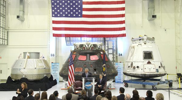 American Flag hanging above three space capsules. Seated crowd being addressed by NASA speakers. Airborne Systems. Design, development, and manufacture of space parachute & inflatable systems. Military-grade deceleration, airbag landing, aerospace recovery, personnel & cargo delivery parachute systems.