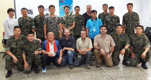 Airborne Systems - Military Parachute Training. Troop and cargo parachute certification for army riggers & jumpers. Instruction for oxygen and JPADS systems. Korea course students and faculty pose in two rows - 18 men 1 woman.