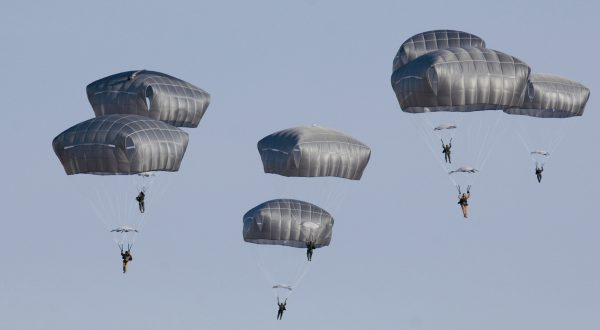 Troop Parachute Training - T-11, MC-6 Airborne Systems - T-11 Static Line Troop Parachute System. T-11 Army Troop Parachute non-steerable for military jumpers. Carries an all-up weight of 400 lbs. Max deployment altitude of 7500 ft. 7 paratroopers descending, blue sky.