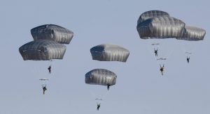 Airborne Systems. T-11, MC-6. Military troop parachute training. Reserve non-steerable parachute systems for riggers & jumpers. Free fall skills & combo drop army missions training. Blue sky with 7 troop parachutes in free fall.