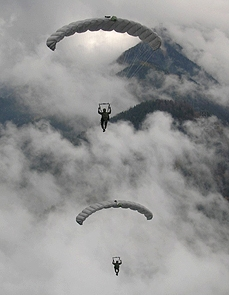 Airborne Systems - Intruder RA-1 Army Ram Air Parachute system for military special forces and beginner jumpers. Carries 450 lbs. Max deployment altitude 25,000 ft. 2 jumpers open canopies, cloudy sky.