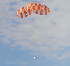 Airborne Systems Space Parachute System. Inflatable parachute systems for spacecraft. Space parachute & inflatable systems. Military-grade deceleration, airbag landing, aerospace recovery, personnel & cargo delivery parachute systems. Custom design and development of military-grade Entry, Descent & Landing Systems (EDLS) for commercial spacecraft.. Three red and white striped canopies with test capsule with billowy clouds. NASA test for Orion.