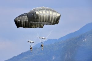 Airborne Systems T-11 Static Line Troop Parachute System. T-11 Army Troop Parachute non-steerable for military jumpers. Carries an all-up weight of 400 lbs. Max deployment altitude of 7500 ft. 2 Soldiers / paratroopers descending to land, and mountains in background. Mountain descent.