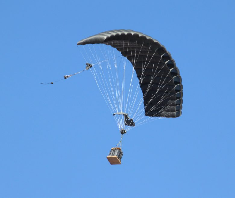 Airborne Systems FireFly Army Cargo Delivery Parachute System. JPADS 2K System of Choice. Carries unmanned loads up to 2,200 lbs. Max deployment altitude 24,500 ft. Canopy and cargo with blue sky.