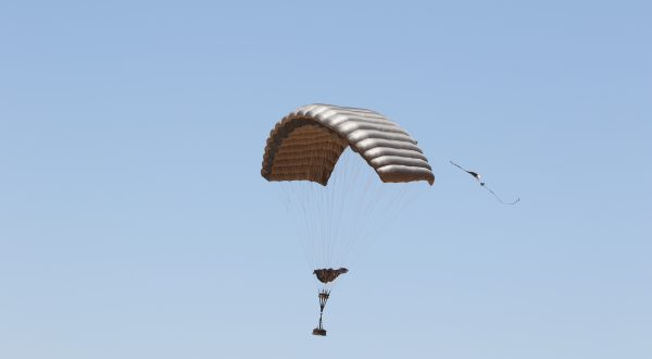 Airborne Systems - 2K1T Army cargo delivery parachute system. Low-cost canopy for one-time use. Drop loads up to 2,200 lbs. Max Deployment altitude 25,000 ft. Military cargo and canopy, blue sky.