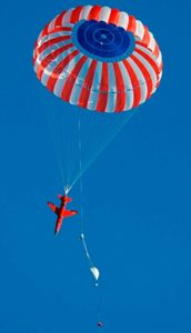 Airborne Systems. Aircraft landing deceleration systems. Design and manufacture of military-grade parachutes. Entry, Descent & Landing System (EDLS) for aircraft. Red plane vertical descent dragging red white and blue striped canopy. Aerial targets.