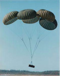Airborne Systems G-12 Military-grade deceleration, airbag landing, aerospace recovery, personnel & cargo delivery parachute systems. Five green canopies landing with cargo. Army Cargo delivery system. JPADS / GPADS: Guided Precision Aerial Delivery System.