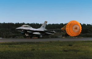 Airborne Systems aircraft Aircraft landing deceleration systems. Design and manufacture of military-grade parachutes. Entry, Descent & Landing System (EDLS) for aircraft. Airplane landing dragging firey orange parachute.