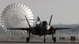 Airborne Systems Aircraft landing deceleration systems. Grey aircraft f-35 dragging inflated decelaration canopy. Design and manufacture of military-grade parachutes. Entry, Descent & Landing System (EDLS) for aircraft. Headon view.