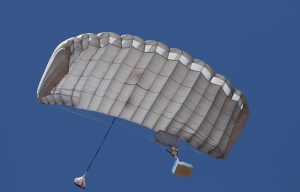 Airborne Systems. FC Mini Army cargo delivery parachute system. JPADS / GPADS: Guided Precision Aerial Delivery System. Carries 200-500 lbs. Max deployment altitude 24,500 ft. White canopy and moderate payload viewed from below.