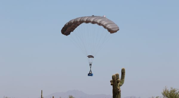 Airborne Systems. FC Mini Army cargo delivery parachute system. JPADS / GPADS: Guided Precision Aerial Delivery System. Carries 200-500 lbs. Max deployment altitude 24,500 ft. Canopy with moderate payload landing with cactus in foreground and mountains behind.