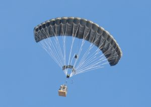 Airborne Systems - FireFly Army Cargo Delivery Parachute System. JPADS 2K System of Choice. Carries unmanned loads up to 2,200 lbs. Max deployment altitude 24,500 ft. Military cargo and inflated canopy, blue sky.