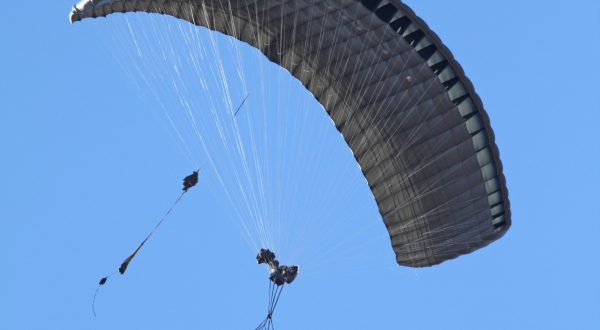 Airborne Systems - FireFly Army Cargo Delivery Parachute System. JPADS 2K System of Choice. Carries unmanned loads up to 2,200 lbs. Max deployment altitude 24,500 ft. Military cargo and inflated canopy from below, blue sky.