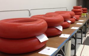 Airborne Systems Inflatable space parachutes. Design, development, and manufacture of inflatable parachute systems for aerospace structures used by the military and NASA. 15+ red inflatable units stacked in rows upon tables.