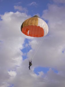 Airborne Systems Ejection parachute. Military-grade deceleration, airbag landing, aerospace recovery, personnel & cargo delivery parachute systems. Military jumper descending, orange brown and white canopy with cloudy blue sky.