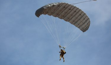 Airborne Systems - Hi-5 Army Military Ram Air Parachute Personnel product system for military special forces jumpers with glide modulation. Carries 485 lbs. Max deployment altitude 25,000 feet. Paratrooper deployed parachute blue sky.