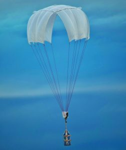 Airborne Systems Unicross Army cargo delivery parachute system. GPADS / JPADS. Low cost, modular design for one-time use or quick repack. Three sizes carry payloads of 75 lbs to 3,200 lbs. White canopy with cargo and blue sky.