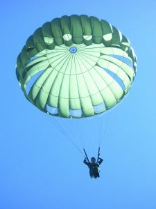Airborne Systems MC-6 Army Troop Parachute non-steerable for military jumpers. Low opening. Carries up to 400 lbs. Minimum deployment altitude 500 ft. Canopy (green) and jumper, blue sky.