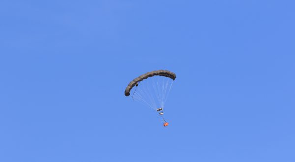 Airborne Systems MicroFly II Army Cargo delivery system. JPADS / GPADS: Guided Precision MilitaryAerial Delivery System. Use with any Airborne Systems Ram Air Canopy. Canopy flying at a distance with orange cargo box and blue sky.