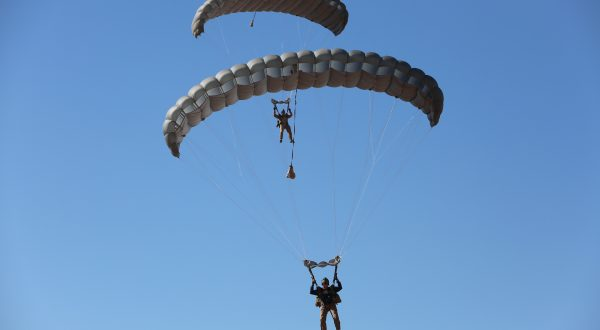 Airborne Systems - MMS Multi-mission Army Ram Air Parachute system for military special forces jumpers. Carries 450-485 lbs. Max deployment altitude 25,000 ft. 2 Jumpers and Ram Air canopies, blue sky.