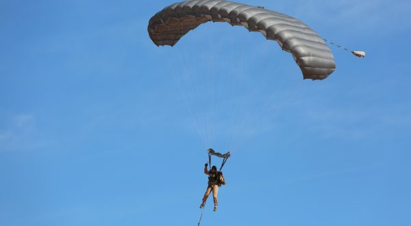 Airborne Systems - MMS Multi-mission Army Ram Air Parachute system for military special forces jumpers. Carries 450-485 lbs. Max deployment altitude 25,000 ft. Jumper and Ram Air canopy, blue sky.
