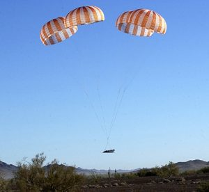 Airborne Systems - Space recovery parachutes systems. Flotation devices and landing systems. Capsule, booster, and payload recovery systems for spacecraft equipment. Nasa pad abort demonstrator landing in desert with mountains behind and 4 red and white canopies.