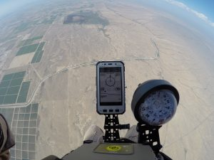 Airborne Systems jTrax Navaid Parachute Navigation System for army and military jumpers and JPADS and GPADS cargo guided precision aerial delivery systems. Close up of device and compass with at aircraft exit, land in background.