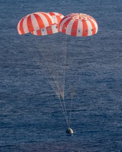 Airborne Systems - Space recovery parachutes systems. Flotation devices and landing systems. Capsule, booster, and payload recovery systems for spacecraft equipment. Space capsule landing in blue ocean with 3 red and white canopies.Crew module splashing down during EFT-1 in the Pacific ocean.
