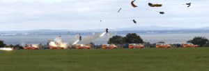 Airborne Systems Ejection Seat test operation on land. Design and manufacture of military-grade parachutes. Entry, Descent & Landing System (EDLS) for aircraft. Grass in foreground, open water behind.