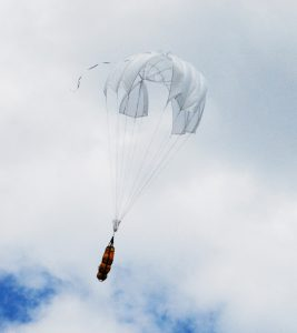 Airborne Systems Unicross Army / military cargo delivery parachute system. Low cost, modular design for one-time use or quick repack. Three sizes carry payloads of 75 lbs to 3,200 lbs. Canopy and orange cargo bags flying with blue sky and clouds.