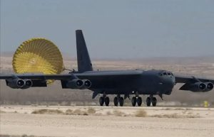 Airborne Systems. Aircraft landing deceleration systems. Grey aircraft f-35 dragging inflated decelaration canopy. Design and manufacture of military-grade parachutes. Entry, Descent & Landing System (EDLS) for aircraft. Huge grey aircraft dragging yellow chute.