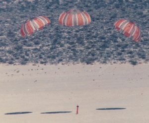 Airborne Systems. Space parachute & inflatable systems. Military-grade deceleration, airbag landing, aerospace recovery, personnel & cargo delivery parachute systems. Atmospheric reentry demonstrator on beach with three red striped parachutes. Atmospheric reentry demonstrator.