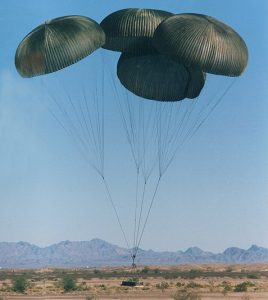 Airborne Systems G-12 Military-grade deceleration, airbag landing, aerospace recovery, personnel & cargo delivery parachute systems. Four green canopies landing with cargo. Army Cargo delivery system. JPADS / GPADS: Guided Precision Aerial Delivery System.
