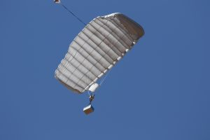 Airborne Systems - FC Mini Army cargo delivery parachute system. JPADS / GPADS: Guided Precision Aerial Delivery System. Carries 200-500 lbs. Max deployment altitude 24,500 ft. Military Cargo and inflated canopy, blue sky.