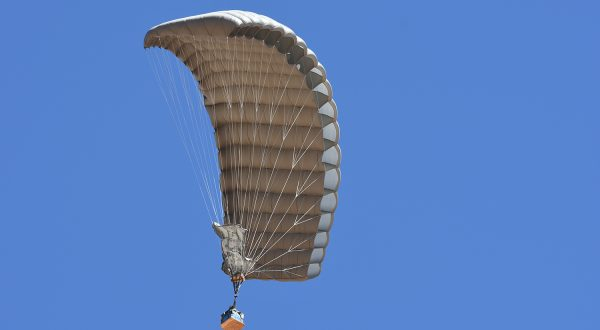 Airborne Systems - FlyClops Army Cargo delivery parachute: one-time use GPADS / JPADS. Carries payloads from 750-2200 lbs. Max deployment altitude 17,500 ft. Military cargo and canopy from below, blue sky.
