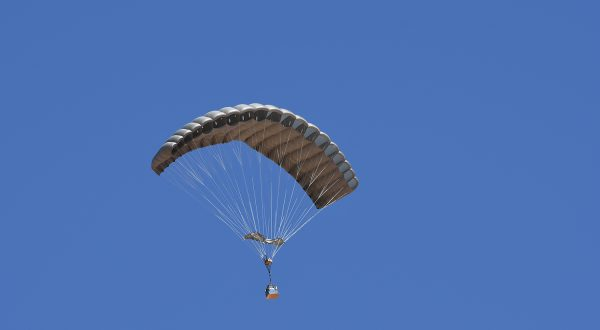 Airborne Systems - FlyClops Army Cargo delivery parachute: one-time use GPADS / JPADS. Carries payloads from 750-2200 lbs. Max deployment altitude 17,500 ft. Military cargo and canopy, blue sky.