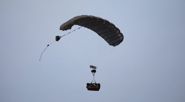 Airborne Systems JPADS and GPADS training courses for military parachute cargo drop missions, army navigation systems for jumpers, and guided precision aerial delivery systems. Deployed canopy with cargo and grey sky.