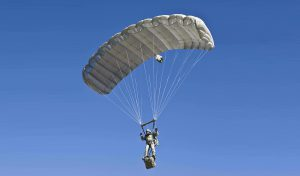 Airborne Systems Intruder RA-1 Army Ram Air Parachute system for military special forces and beginner jumpers. Carries 450 lbs. Max deployment altitude 25,000 ft. Deployed canopy with military jumper / gear bag and blue sky.