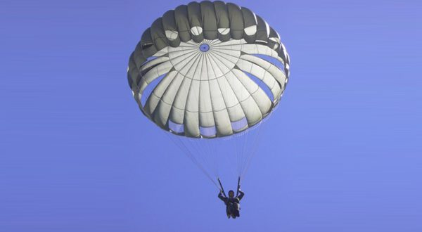 Airborne Systems MC-6 Army Troop Parachute non-steerable for military jumpers. Low opening. Carries up to 400 lbs. Minimum deployment altitude 500 ft. Static line parachute free fall military jumper open canopy. From below with blue almost purple sky.