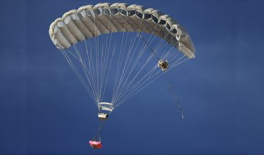 Airborne Systems MicroFly II Army Cargo delivery system. JPADS / GPADS: Guided Precision Aerial Delivery System. Use with any Airborne Systems Ram Air Canopy. Deployed parachute with orange cargo platform and blue sky.