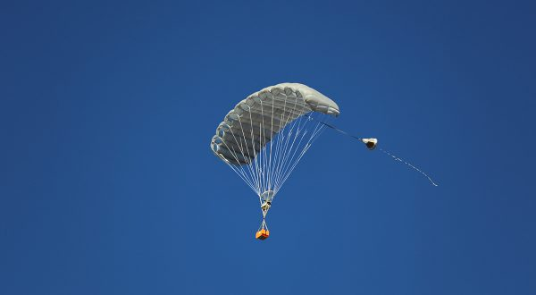 Airborne Systems MicroFly II Army Cargo delivery system. JPADS / GPADS: Guided Precision Aerial Delivery System. Use with any Airborne Systems Ram Air Canopy. Deployed parachute with orange cargo box and blue sky.