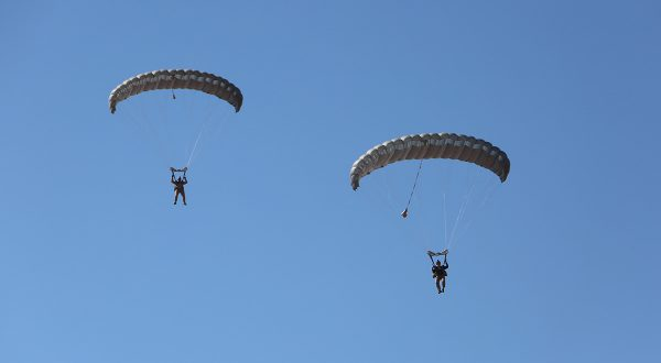 Airborne Systems MicroFly II Army Cargo delivery system. JPADS / GPADS: Guided Precision Aerial Delivery System. Use with any Airborne Systems Ram Air Canopy. Two deployed parachutes with military jumpers and blue sky.