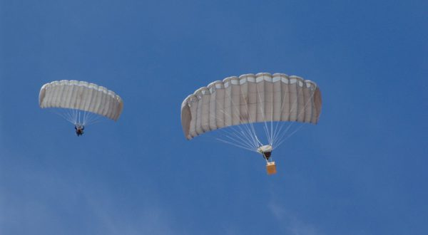 Airborne Systems MicroFly II Army Cargo delivery system. JPADS / GPADS: Guided Precision Aerial Delivery System. Use with any Airborne Systems Ram Air Canopy. Two deployed parachutes from below with one jumper and one white cargo box and blue sky.