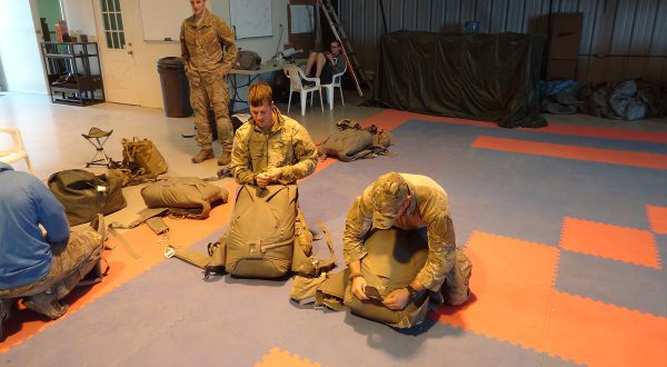Airborne Systems T-11, MC-6. Military troop parachute training. Reserve non-steerable parachute systems for riggers & jumpers. Free fall skills & combo drop army missions training. Riggers repacking parachutes in training facility. 3 military jumpers prep.